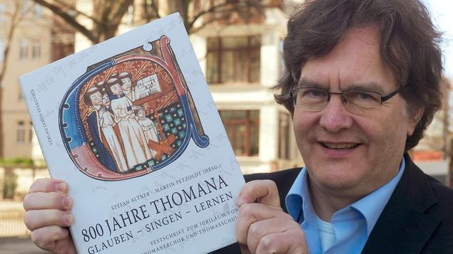 Georg Christoph Biller, der 16. Kantor des Thomanerchores nach Johann Sebabestian Bach, mit der Festschrift zum 800-jährigen Bestehen des Thomanerchores. - FOTO: PETER ENDIG DPA/LSN